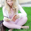 Cute woman sitting on the grass and reading the book — Stock Photo