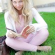 Stock Photo: Cute womsitting on grass and reading book