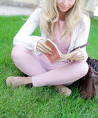 Young woman sitting with book grass — Stock Photo