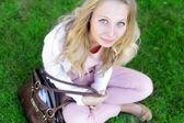Insouciante femme assise dans un champ vert — Photo