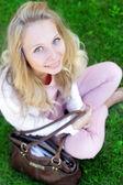 Donna spensierata seduto in un campo verde — Foto Stock