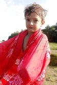 Beautiful boy portrait in red towel outdoors — Стоковое фото