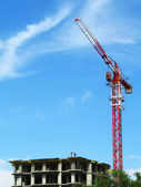 Crane and building construction site against blue sky — Stock Photo