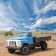 Stock Photo: Old blue farm truck fading in time in desert