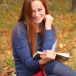 Young beautiful girl with red hair reading a book — Stock Photo #13747914