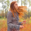 Beautiful redhead in a autumn meadow — Stock Photo