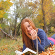 Redhead  young university student studying lying down in grass. — Stockfoto