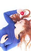 Redhead girl with red apple, focus on apple — Stock Photo