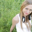 Stock Photo: Womlying on grass with headphones