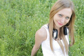 Woman lying on grass with headphones — Stock Photo