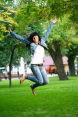 Young woman jamping on a grass — Stock Photo