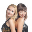 Two attractive girl friends - blond and brunette on white background back to back in party dress — Stock Photo #20296975