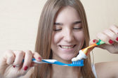 Closeup on woman's toothy smile brushing her teeth — Stock Photo