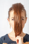 Portrait of a blonde woman with hair before face — Stock Photo