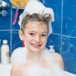 Smiling little boy covered with soap bubbles — Stock Photo #22912736