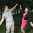Happy young adult couple dancing outdoors at night — ストック写真