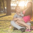 Stock Photo: Romantic young couple relaxing on grass