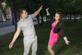 Happy young adult couple dancing outdoors at night — Stock Photo