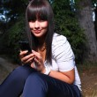 Smiling teenage girl shows cell — Stock Photo #25610511