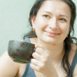 Woman smiling drinking tea indoors — Stock Photo #25611105