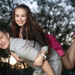 Young couple piggybacking in park — Stock Photo