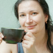 Woman smiling drinking tea front view — Stock Photo #25612757
