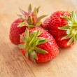 Three strawberries on wooden table — Stock Photo