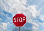Dirty old red British Stop sign and blue sky. — Stock Photo