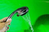 Chuveiro com queda de gotas de água sobre o fundo verde. — Fotografia Stock