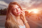 Beautiful girl in the street at evening or night, sunset light on baclgroundon the roof — Stock Photo