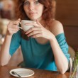 Redhead women sitting in the cafee and holding cup of coffee — Stock Photo #31685339