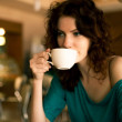Redhead women sitting in the cafee and holding cup of coffee — Stock Photo #31685365