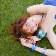 Pretty redhead lay on the grass — Stock Photo
