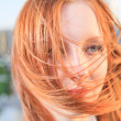 Candid closeup portrait of the young sexy redhead woman with flying hair — Stock Photo #31704823