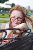 Beautiful young female sitting on the bench in summer park — Stock Photo