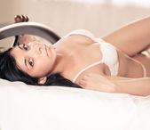 Pretty brunette women in bed — Stock Photo