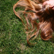 Young woman with long blond hair lying on the grass sleeping or thinking. — Stock Photo