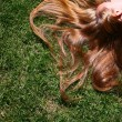 Young woman with long blond hair lying on the grass sleeping or thinking. — Stock Photo #32584557