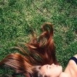 Young woman with long blond hair lying on the grass sleeping or thinking. — Stock Photo #32584575