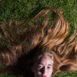 Beautiful young girl is lying on green grass — Stock Photo