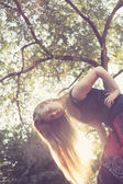 Blonde women at sunset backlit near tree — Stock Photo
