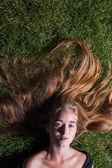 Hermosa joven está tumbado en la hierba verde — Foto de Stock