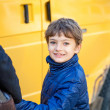 Portrait of happy kid looking back at camera on his way to school — Stockfoto