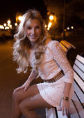Blonde on bench at night — 图库照片