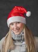 Pretty blond wearing christmas hat on dark background — Stock Photo