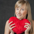 Beautiful young woman holding a heart shaped red pillow and smiling — Stock Photo #33750683