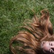 Cute young female lying on grass field at the park evening — Stock Photo