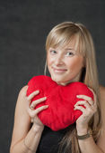 Beautiful young woman holding a heart shaped red pillow and smiling — Stock Photo