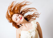 Red haired expressive emotional female with flying hair on studio background — Stock Photo