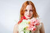 Vackra rödhåriga flicka med blommor studio skott — Stockfoto